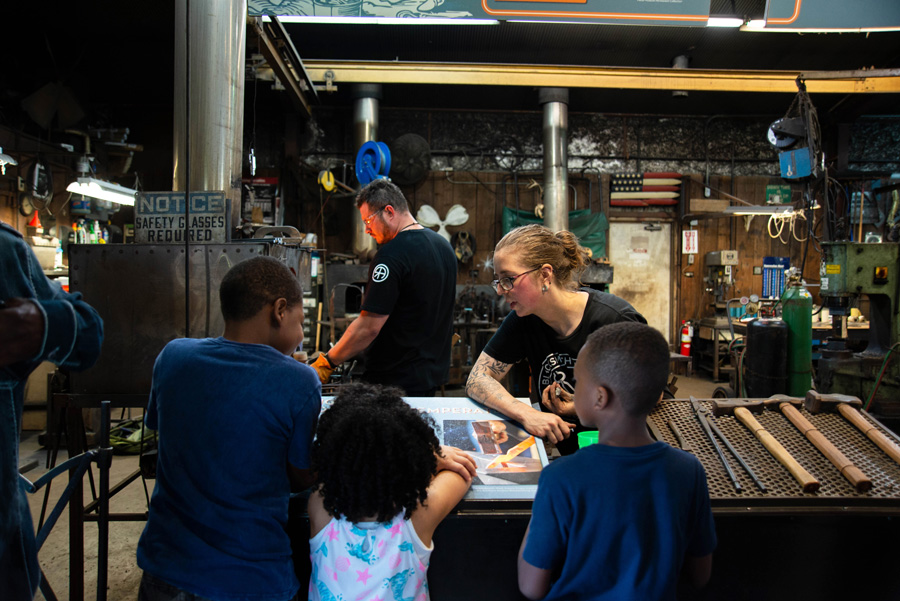Blacksmithing apprentice Elizabeth Belz speaks to a group of children about blacksmithing in the shop during an after-hours event. Photo courtesy of the Metal Museum.